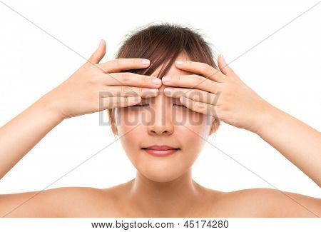 Skin care woman putting eye cream touching upper eyes. Facial beauty closeup of beautiful mixed race Asian female model isolated on white background.