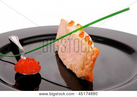 savory fish : norwegian salmon fillet roasted with green onion pen , red caviar in spoon , on black dish isolated over white background