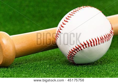 Close-up of wooden bat and baseball ball on artificial green grass