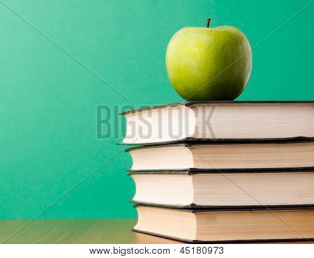 Green apple on a pile of books , isolated on green background