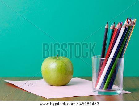 Pencils on a glasses, green apple and paper on the desk