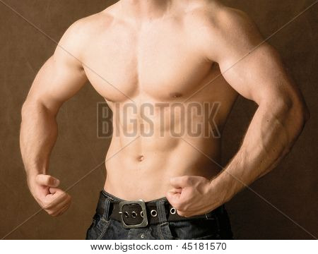 Muscular man, isolated on brown background