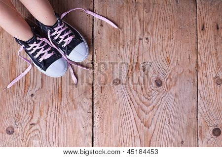 Child Feet In Sneekers On Old Wooden Floor