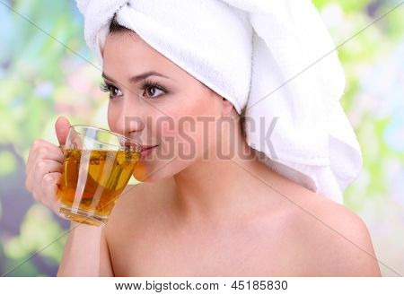 Beautiful young woman with cup of herbal tea on bright background