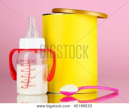 Bottle with milk and food for babies on pink background