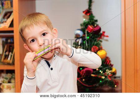 Süße kleine Junge spielt auf der Mundharmonika