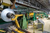 Roll of aluminum rotates on machine in workshop on rolling mill