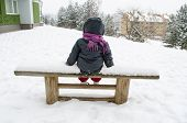 picture of outerwear  - child with a dark gray jacket and purple scarf sitting on a bench abundant snow in the distance snow pines top - JPG