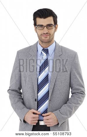 Portrait of elegant young businessman, looking at camera, smiling, wearing glasses.