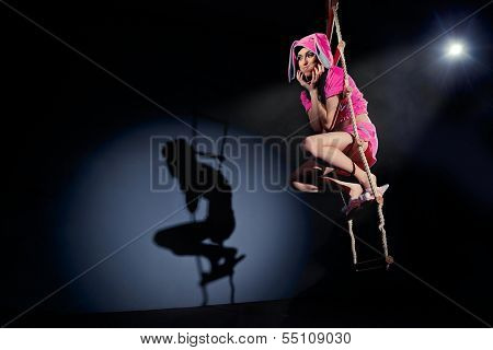 Funny pink rabbit sitting on rope ladder