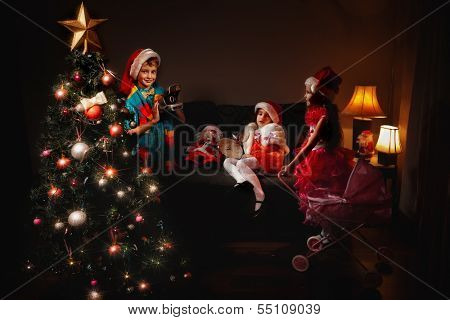 Group of children in Christmas hat with adorable girl play with toy carriage and boy make a picture