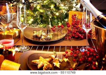 Christmas And New Year Holiday Table Setting with Champagne. Celebration. Place setting for Christmas Dinner. Holiday Decorations. Decor.