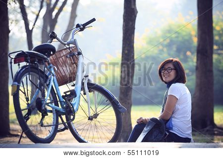 asian woman sitting in the park with bicycle in morning use for helathy life and relaxing in holiday