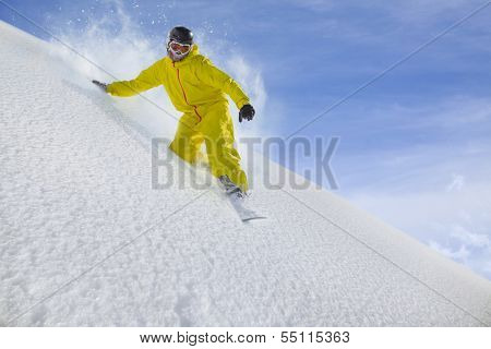 Snowboard freerider moving down in snow powder
