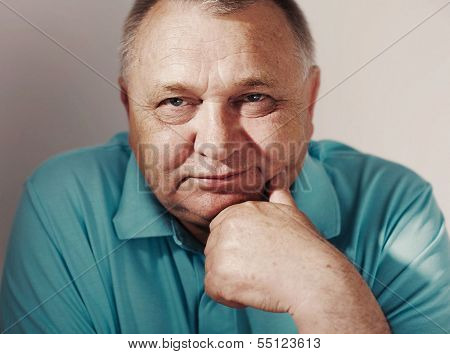 Toned close up portrait of middle aged man with hand near chin on white background