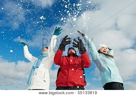 Young people having fun with snow in winter outdoors