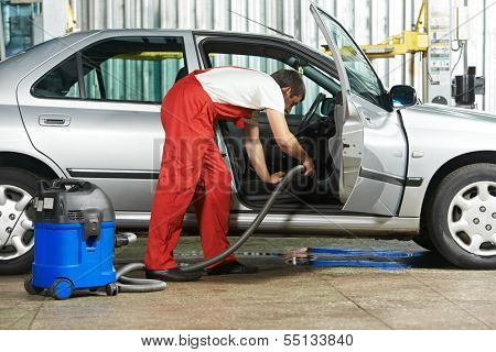 Automobile cleaning theme. Mechanic hoovering the car cabin with vacuum cleaner at auto repair shop garage