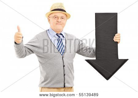 Smiling senior man holding a black arrow pointing down and giving a thumb up isolated on white background