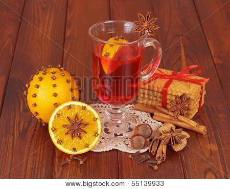 Glass of mulled wine on napkin and orange