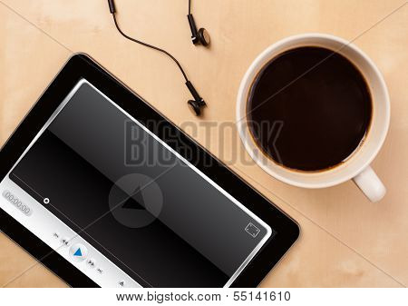 Workplace with tablet pc showing media player and a cup of coffee on a wooden work table close-up