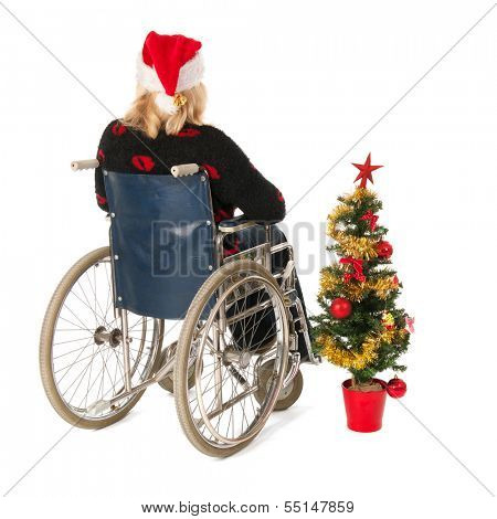 Blond woman in wheelchair with Christmas tree isolated over white background