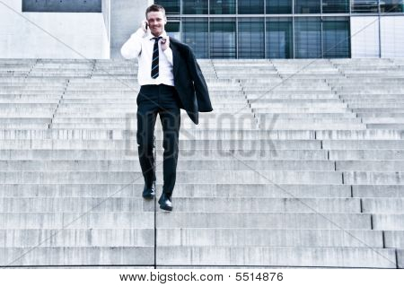 Corporate Man With Cellular Phone On Stairs
