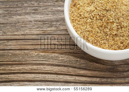 golden flaxseed meal - a ceramic bowl on grained wood background