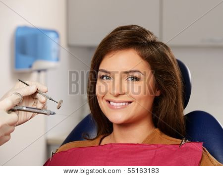 Dentist making anaesthetic injection to woman patient