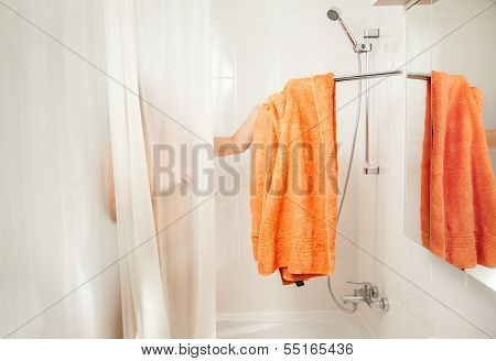 Woman in shower taking off orange towel