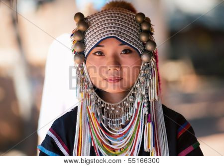 CHIANG RAI, THAILAND - DEC 4 : Akha girl with traditional clothes and silver jewelery in akha hitt tribe minority village on December 4, 2013 in Chiang Rai, Thailand.