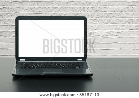Laptop With Blank Screen On Wooden Table At Brick Wall
