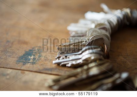 Many old keys on a well used old wooden desk. Security and encryption, concept image.