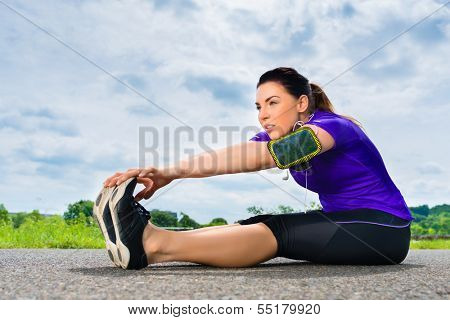 Urban sports - young woman is doing warming up before running in the greenfield on a summer day