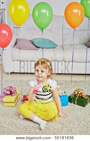 Little girl sits on light carpet in room with big sofa holding party-blower in her hand, gift boxes and birthday air balloons are behind her