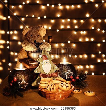 Image of traditional x-mas toys on glowing lights background, Christmastime decorations still life, teddy bear, candles, decorative Christmas tree and homemade cookies on the holiday table
