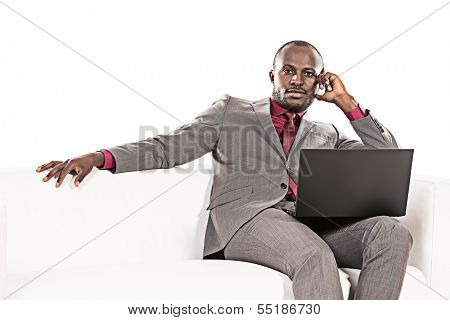 Portrait of a handsome african american business man working on his laptop on a sofa. Isolated over white.