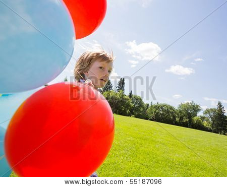 Young boy with helium balloons in park