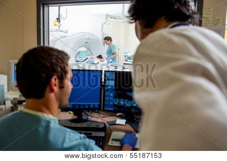 Radiologist and nurse operating computers while nurse preparing patient for CT scan in hospital