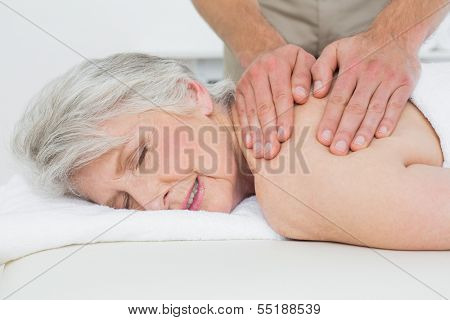 Close-up of a physiotherapist massaging a senior woman's back in the medical office