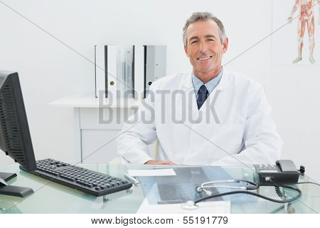 Portrait of a smiling confident male doctor sitting at desk in medical office