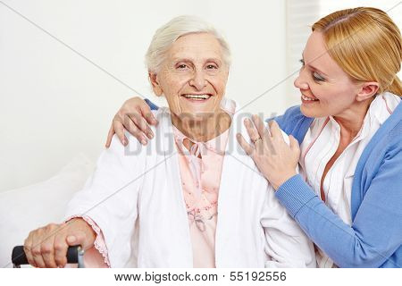 Happy senior woman getting geriatric care at home from her daughter