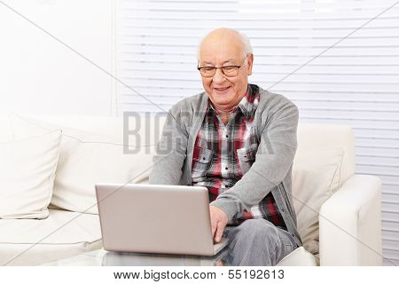 Happy senior citizen man working with computer in the internet