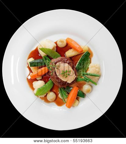 Tenderloin steak with vegetables and bone marrow isolated on black background