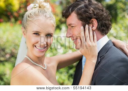 Pretty wife touching her new husbands cheek smiling at camera in the countryside