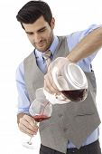 Sommelier pouring wine from decanting carafe to wineglass.