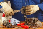 picture of carburetor  - Serviceman repairing the old car engine carburetor - JPG
