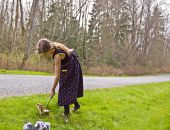 image of pick up  - 8 year old Caucasian girl is doing her share by cleaning up litter and garbage on a roadside to help the environment - JPG