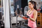 stock photo of pulley  - Pretty young woman using a pulley to tone her muscles in a gym ** Note: Shallow depth of field ** Note: Slight graininess, best at smaller sizes - JPG