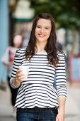 Portrait of beautiful woman holding disposable coffee cup outdoors