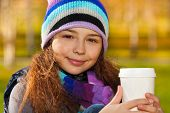 foto of 11 year old  - Close portrait of nice smiling 11 years old girl holding coffee mug wearing blue purple hat and scurf